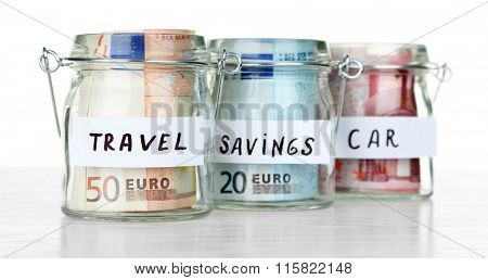 Three jars for different needs full of coins