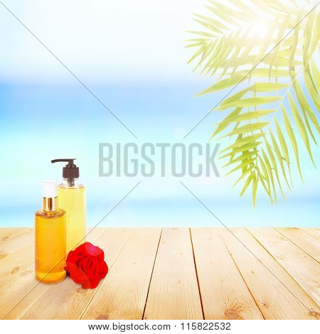 Bottles with suntan cosmetics on wooden board on sea background