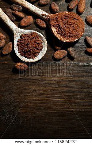 Spoon with aromatic cocoa and chocolate on wooden background, close up