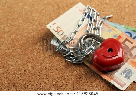 Euro banknotes with lock and chain on wooden background