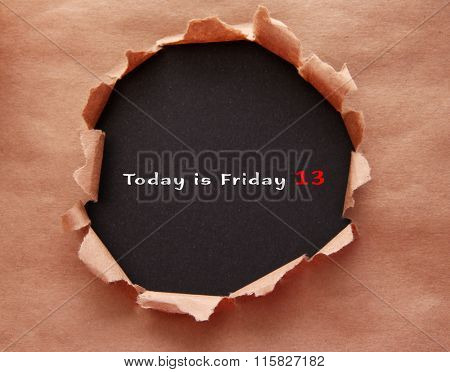 Torn craft paper with black background and text Today is Friday 13