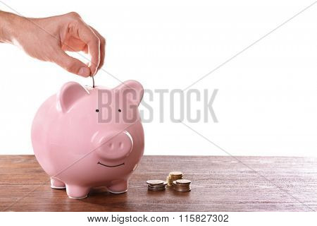 Man putting coin in pig moneybox