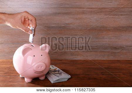 Man putting dollar banknote in pig moneybox