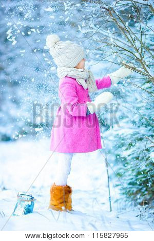 Little girl with flashlight and candle in winter on Christmas eve outdoors