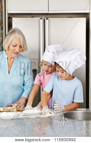 Two children baking christmas cookies with their grandmother in a kitchen