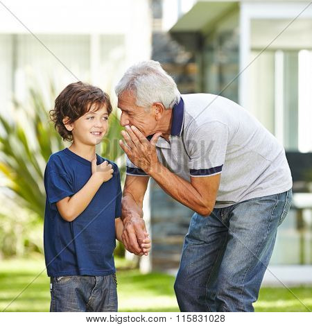 Grandfather whispering a wish in the ear of his grandson in a garden