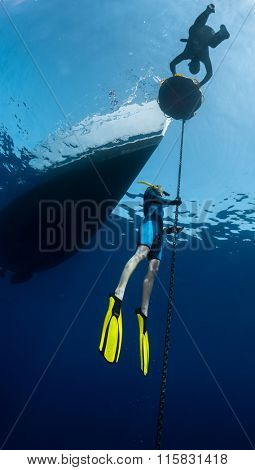 Lady free diver ascending along the metal chain linked to the boat