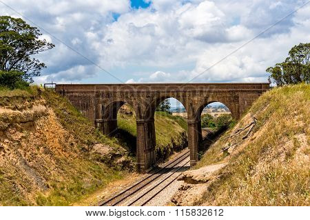Picturesque old arch bridge viaduct with railway track underneath. Tarana road NSW Australia