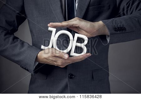 Businessman In Suit With Two Hands In Position To Protect The Word