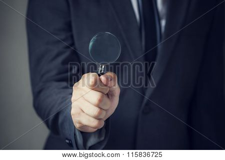 Businessman In Suit Looking For Something Using A Small Magnifier. It Indicates Many Aspects Such As