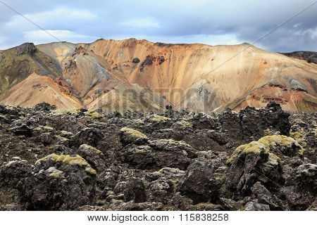 Pieces of gray and black lava, sometimes covered with green moss. In the background - blue and orange rhyolite mountains. National Park Landmannalaugar in Iceland