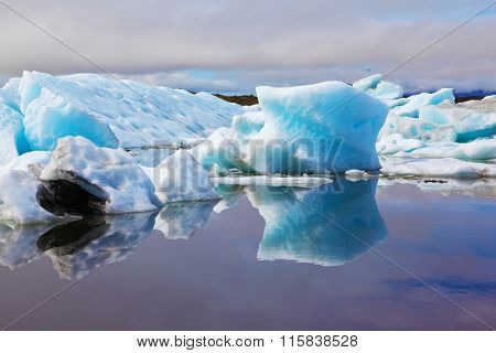 Blue and emerald icebergs and ice floes are reflected in smooth water of the Gulf Yokulsarlon in Iceland. Sunrise. Reflection.