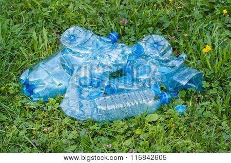 Plastic Bottles And Bottle Caps On Grass In Park, Littering Of Environment