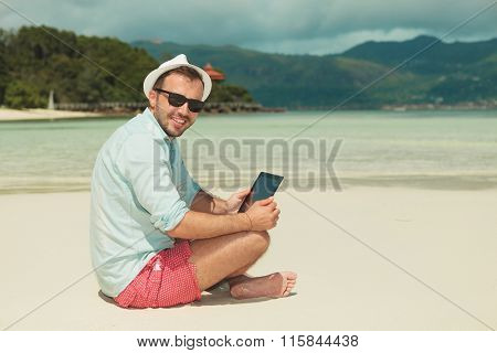man sitting on the shore with legs crossed reading from an ipad while posing to the camera