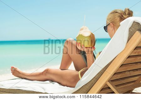 blonde girl holding coconut and reading on the beach while lying down on sunbed