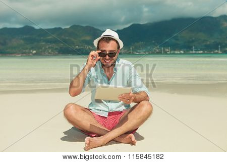young man on the beach smiling and fixing his sunglasses while holding ipad