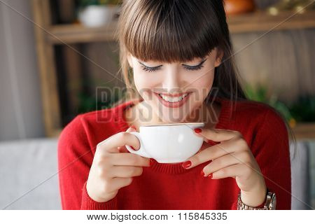 Girl with a Cup of hot tea at a table in a cafe