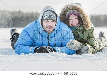 Young couple having fun outdoors lying on snowy ground covering in winter snowing day