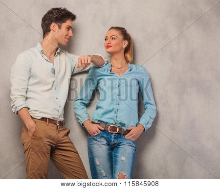 attractive man with hand in pocket lean on girl shoulder while she looks at him with hands in pockets in studio background