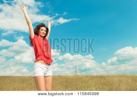 happy girl jumping in the fields with her hands raised in the air while smiling and looking away