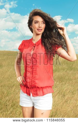 beautiful woman wearing red blouse and white shorts, touching her hair while looking away off the camera