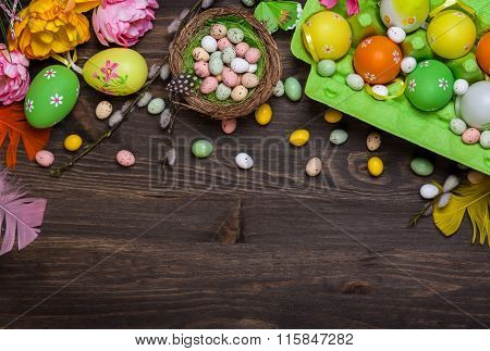Easter decorations  with colorful eggs and sweet candy over wooden background