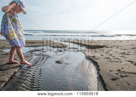 BALI INDONESIA - 15 JAN - an unidentified young little girl dipping barefoot into water at the beach