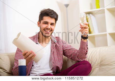Young man sitting on the sofa and holding in his hand university degree, toasts