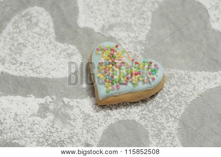 Cookie With Blue Icing On Baking Paper Powdered With Sugar