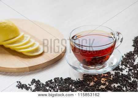 Black tea in a transparent glass bowl on a table. Dry black tea scattered on the table. Tea with lemon on a cutting board.
