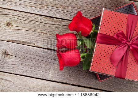 Red roses in Valentines day gift box on wooden background. Top view with copy space