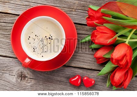 Red tulips, coffee cup and Valentines day candy hearts on wooden table