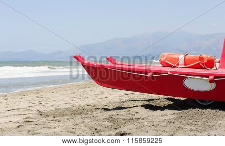 Small red life guard vessel is parking next to the sea