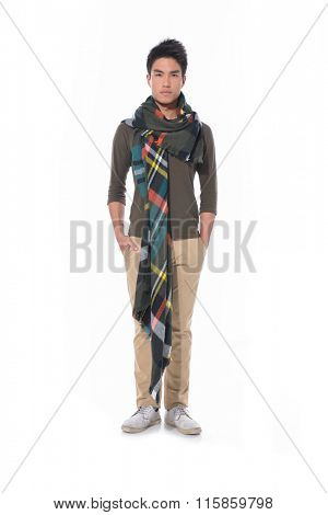 Full length portrait of young man with scarf standing with hands in pockets