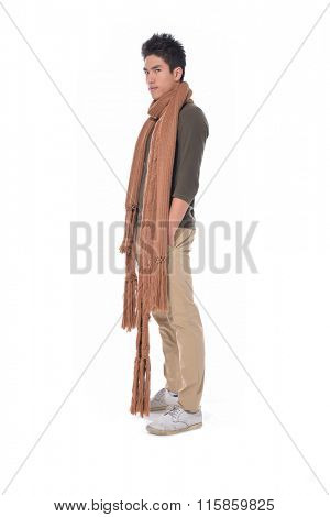 portrait of side view young man with scarf standing with hands in pockets