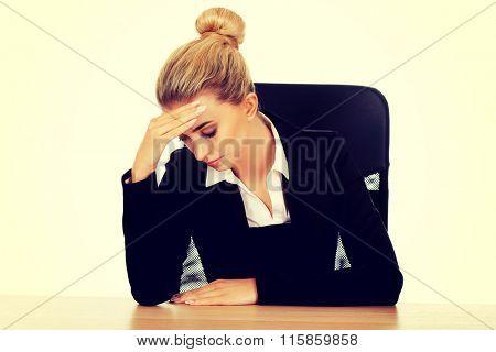 Beautiful worried businesswoman behind the desk