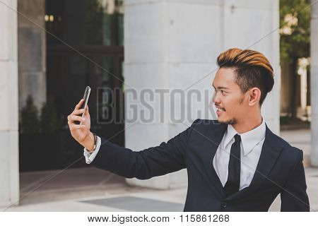 Young Handsome Asian Model Taking A Selfie In The City Streets