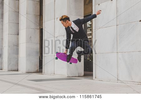 Young Handsome Asian Model Jumping With His Skateboard
