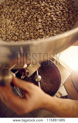 Hands of a coffee roaster operating an appliance with beans