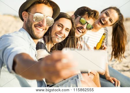 Group of friends at the beach making a selfie together