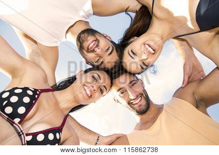 Multicultural group of friends embraced together at the beach
