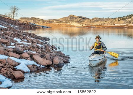 senior male paddling a decked expedition canoe on Horsetooth Reservoir near Fort Collins in northern Colorado, winter scenery