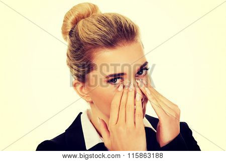 Businesswoman giggles covering her mouth with hand