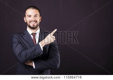 Smiling business man pointing at copy space against dark background