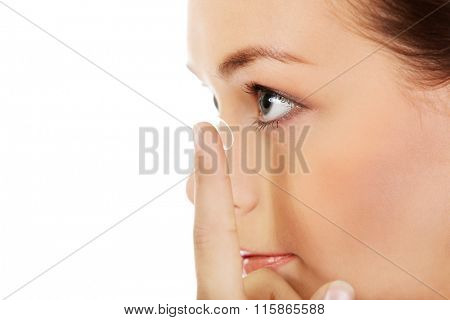Beautiful young woman putting a contact lens