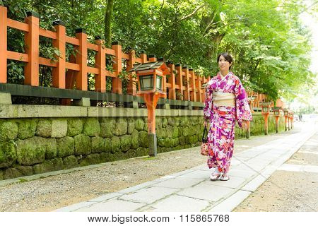 Young Woman wearing the kimono dress and walking the street