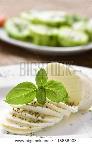 closeup of a plate with a sliced fresh cheese on a table, and a plate with chopped courgette in the background