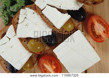 fresh greek feta cheese sandwich on wooden plate with hot green olives and black, goat cube, tomatoes kale over table