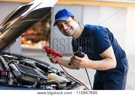 Mechanic using booster cables to startup a car engine