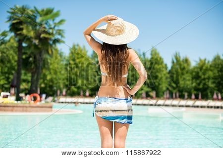 Woman holding her hat on the poolside